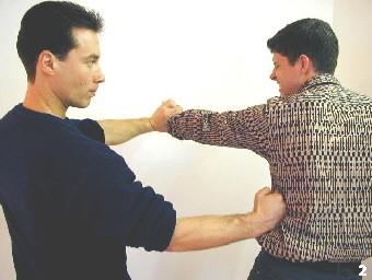 Wing Tsun Selbstverteidigung Gratis Kurs - Der gegnerische Arm wird kontrolliert, während Sifus Schlag die Rippen des Gegners treffen