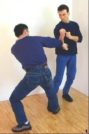 Sifu schütz seine mittlere Körperpartie durch Cham-Sao rechts, wodurch der Arm des Gegners nicht durchdringen kann.