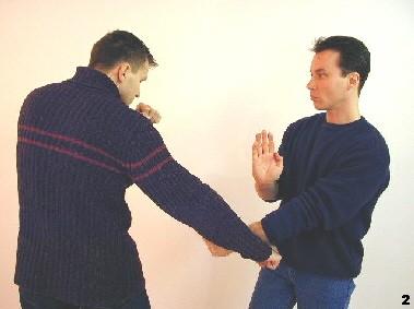 Innenfauststoß tief - Sifu lenkt den tiefen Faustschlag des Gegners durch einen Innenfauststoß ins Leere