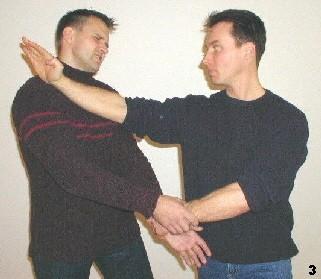Die enge Griffhaltung des Gegners ermöglicht es Sifu, daß er den linken Arm des Gegners mit seiner Linken greift. Der Gegner hält sich sozusagen selbst in Schach. Gleichzeitigt folgt der Konterschlag zm Hals des Gegners mittels Fak-Sao