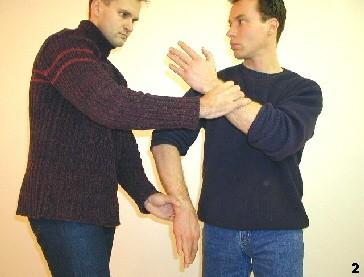 Sifu senkt seine Körper ab und fürht eine Drehbewegung aus, so daß sein rechter Ellbogen über dem Handgelenk des Gegners eine Scherwirkung entfaltet.