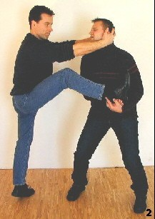 Sifu macht einen kleinen Sprung nach vorn und zieht sich sogleich an den Gegner heran. Das Heranziehen erfolgt sowohl mit dem eigenen Bein, als auch durch den Griff zum Kopf.