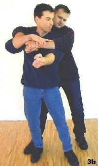 Sifu kontrolliert mit seiner rechten Hand die noch bestehende Umklammerung, während sein linker Arm den Rückwärtsellbogen einleitet.
