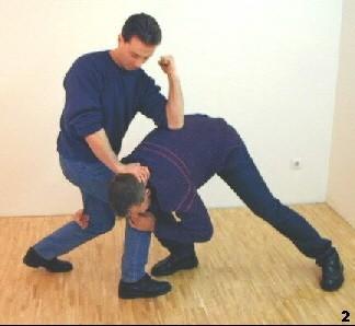 Sifu lässt sein Körpergewicht fallen, drückt den Gegner am Kopf herunter und führt zugleich einen Ellbogen aus.