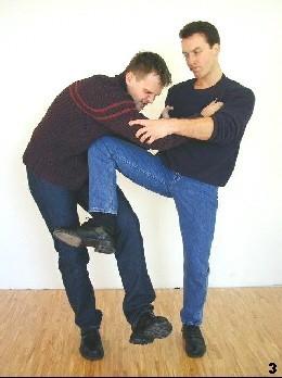 Sifu gleitet mit seinem Bein nach oben und führt die Tan-Gerk-Kniestoßtechnik aus, wodurch er sein Gleichgewicht stabiliseirt und der Gegner getroffen wird.
