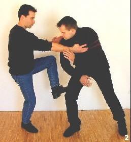 Sifu setzt mit seinem hinteren Bein zum kreuzenden Tritt an. Dabei kontrolliert er zudem die Schulterpartie des Gegners, um diesen an einer Ausrichtung zu hindern.