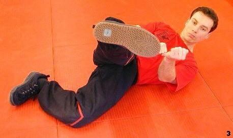 Im letzten Moment wird aus der schützenden Position ein Tritt, das Knie ist dabei einwärts gedreht