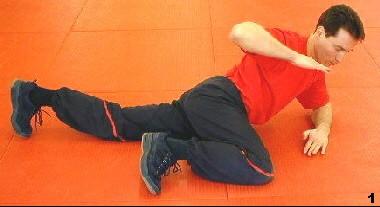 Dreiecksstand - Sifu zieht ein Bein an, während das ander gestreckt ist und er sich mit einem Ellbogen aufstützt