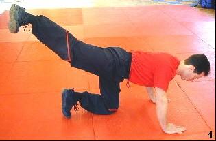 Sifu Dragos  schwingt sein rechtes Bein zurück. Dabei stützt er sich auf seine Arme und einem Knie ab