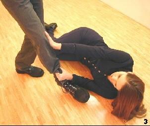 Melanie drückt das Bein des Gegners von der Innenseite in Kniehöhe weg und zieht das untere Fußende an sich heran