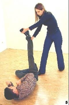Melanie greift das Bein des Gegners und wirft es diagonal über die Schulter des Gegners. Der Gegner wird hierdurch gedreht und angehoben.