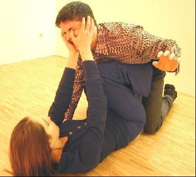 Der Angreifer wird mit den Knien zurückgehalten und zeitgleich mittels Daumenstoß zu den Augen außer Gefecht gesetzt