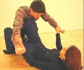 Melanie greift den Arme des Gegners von innen und drückt den Gegner mit ihrem Knie am Brustbein zurück