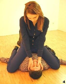 Melanie rollt sich auf den Gegner, kontrolliert diesen mit den Knien und führt einen doppelten Daumenstoß aus.
